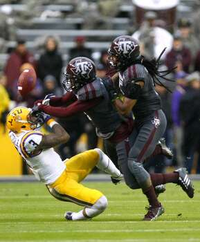 Texas A&M defensive backs De'Vante Harris, center, and Floyd Raven Sr., right, break up a pass intended for LSU wide receiver Odell Beckham Jr. Photo: Cody Duty, Houston Chronicle