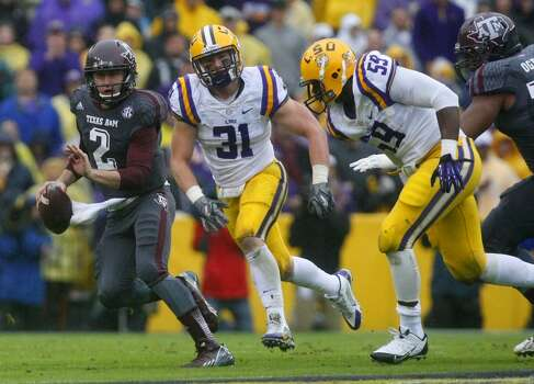 Texas A&M quarterback Johnny Manziel scrambles away from LSU linebacker D.J. Welter, and defensive end Jermauria Rasco. Photo: Cody Duty, Houston Chronicle