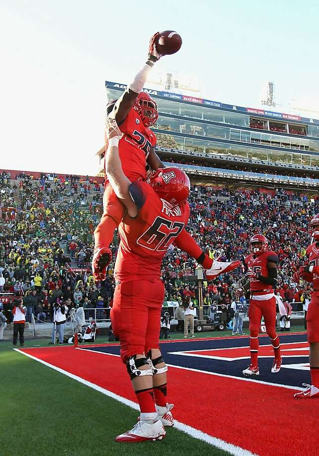Arizona's Ka'Deem Carey is up in arms, specifically those of teammate Chris Putton, over his four-touchdown effort. Photo: Christian Petersen, Getty Images