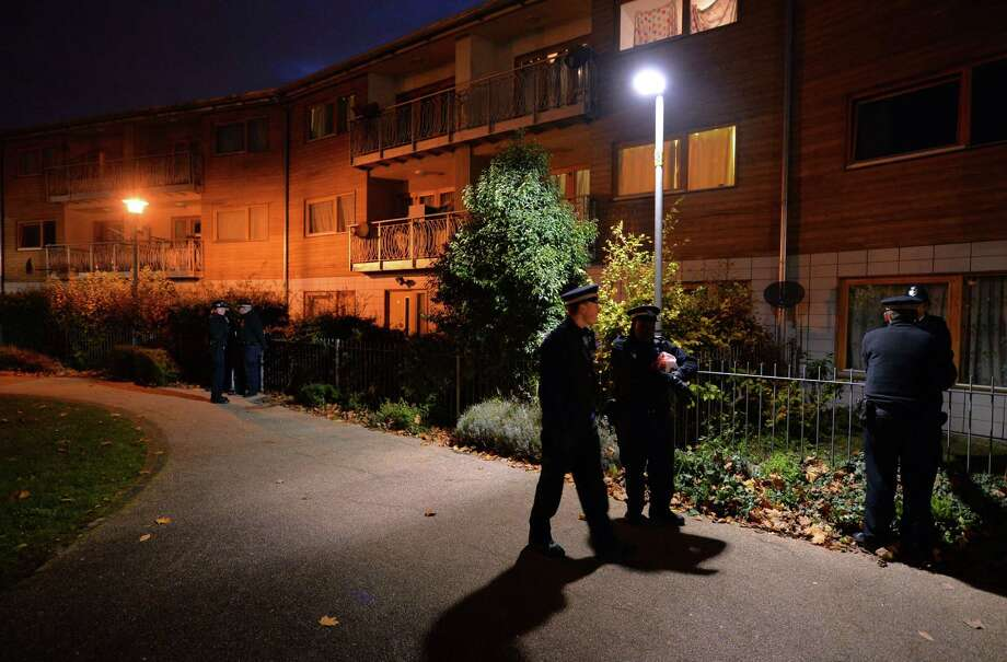 Police guard a block of residential flats in South London as investigators go house-to-house inquiring about three women believed to have been held captive for 30 years by a couple from India and Tanzania. Photo: LEON NEAL, Staff / AFP