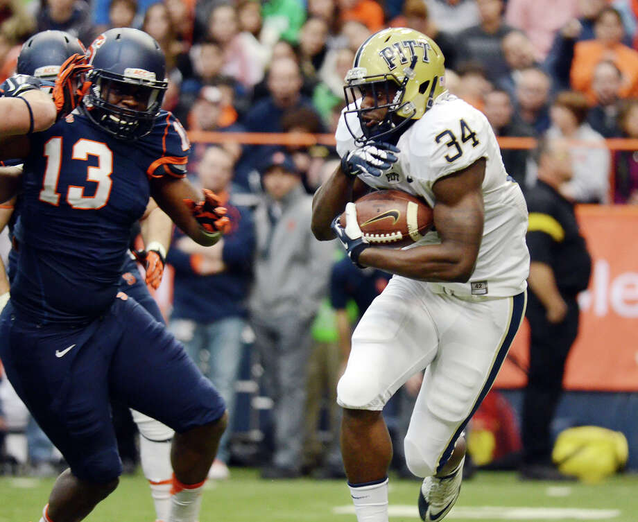 Pittsburgh's Isaac Bennett, right, runs the ball against Syracuse defense an NCAA college football game at the Carrier Dome in Syracuse, N.Y., Saturday, Nov. 23, 2013. Pittsburgh won 17-16. (AP Photo/Heather Ainsworth)   ORG XMIT: NYHA205 Photo: Heather Ainsworth / FR120665 AP
