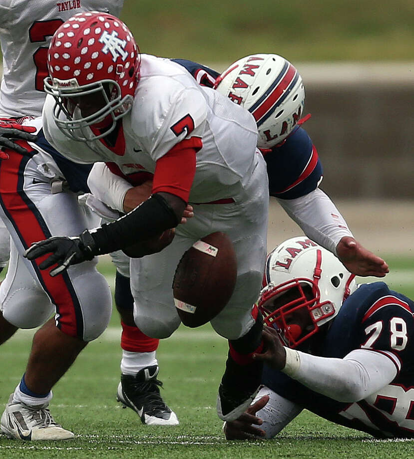 Alief Taylor quarterback Remi Olonade (7) fumbles after being tackled by Lamar's Brandon Agomuo during the first half of a high school football playoff game, Saturday, November 23, 2013, at Delmar Stadium in Houston. Photo: Eric Christian Smith, For The Chronicle