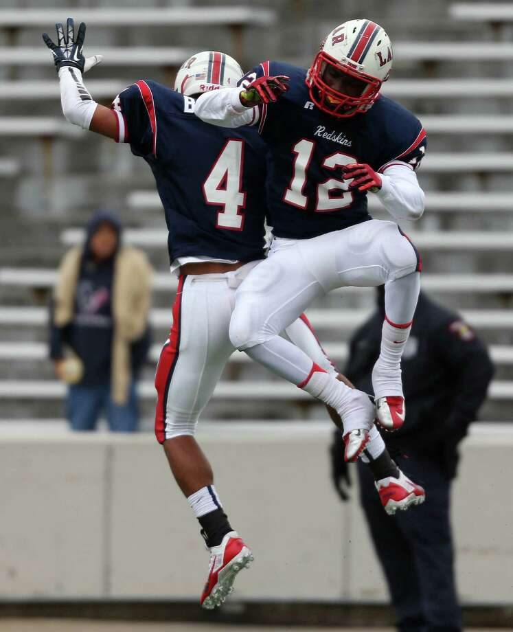 Lamar's Trevion Duncan (12) and John Boney celebrate a defensive stop during the first half of a high school football playoff game against Alief Taylor, Saturday, November 23, 2013, at Delmar Stadium in Houston. Photo: Eric Christian Smith, For The Chronicle