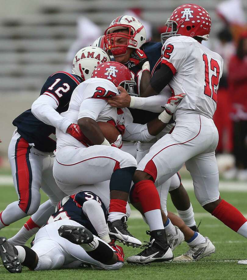 Alief Taylor's Kaleb Campbell (25) is tackled by Lamar's Trevion Duncan (12) during the first half of a high school football playoff game, Saturday, November 23, 2013, at Delmar Stadium in Houston. Photo: Eric Christian Smith, For The Chronicle