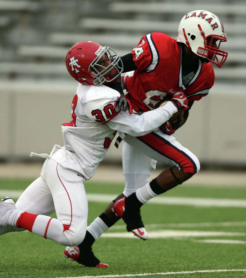 Lamar's Shelby Walker, right, scores a touchdown as Alief Taylor's Noah Iheanacho defends during the second half of a high school football playoff game, Saturday, November 23, 2013, at Delmar Stadium in Houston. Photo: Eric Christian Smith, For The Chronicle