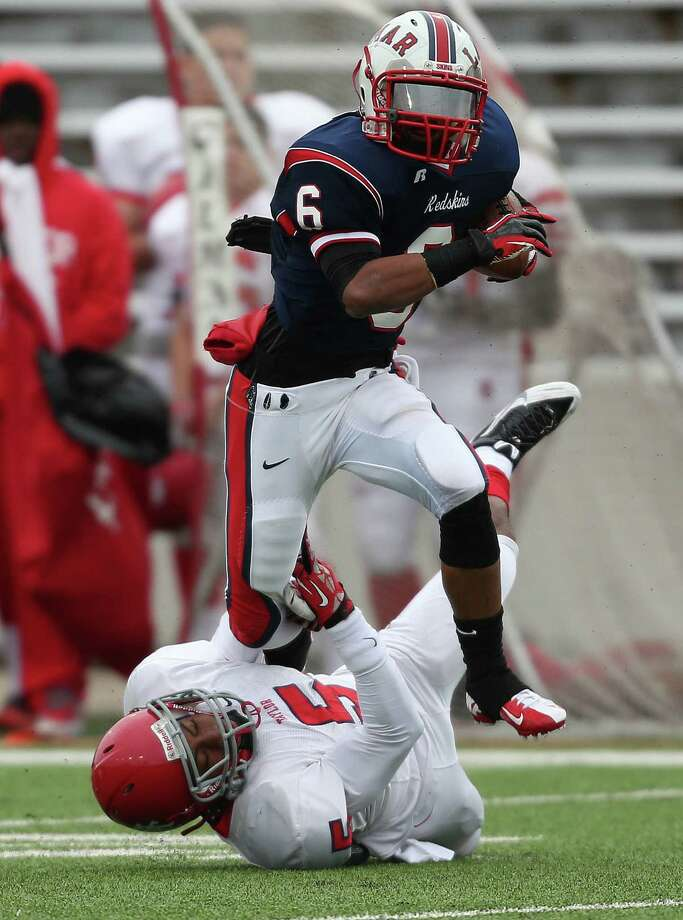Lamar's Nicholas Turner (6) tries to escape the grasp of Alief Taylor's David King during the first half of a high school football playoff game, Saturday, November 23, 2013, at Delmar Stadium in Houston. Photo: Eric Christian Smith, For The Chronicle