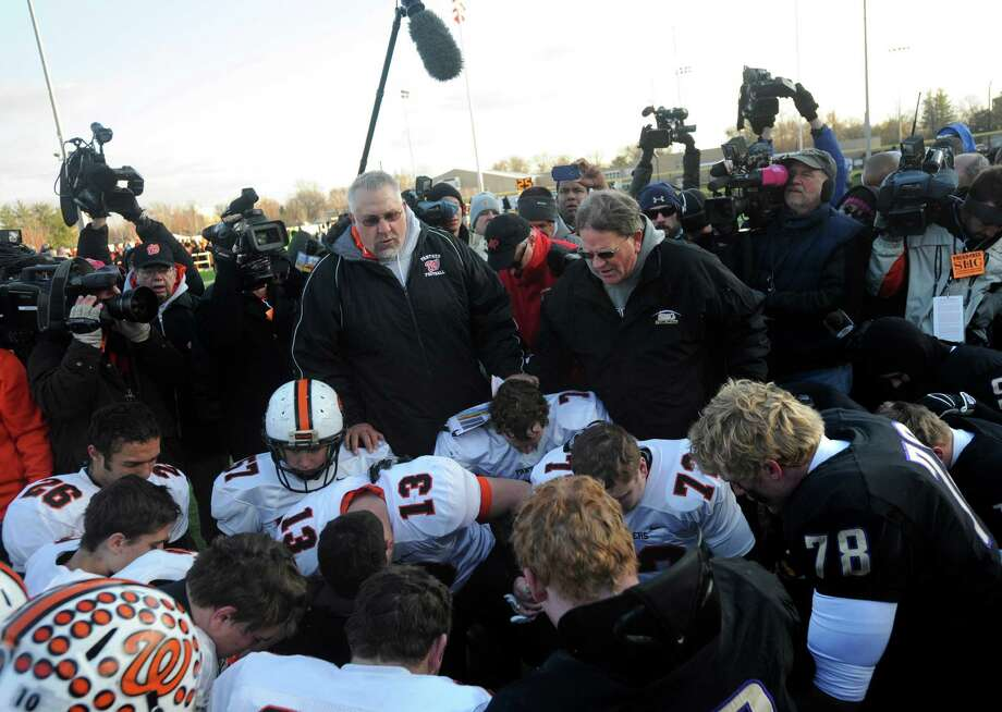 Washington High School head coach Darrell Crouch, left, and Sacred Heart-Griffin head coach Ken Leonard, say a prayer with football players from both teams Saturday Nov. 23, 2013, after a Class 5A football semifinal playoff  game in Springfield, Ill. Washington lost the game, 44-14, but still played the game despite over 10 players on the roster that lost their family home after a tornado tore throughout central Illinois town last Sunday. Photo: RON JOHNSON, AP / Journal Star