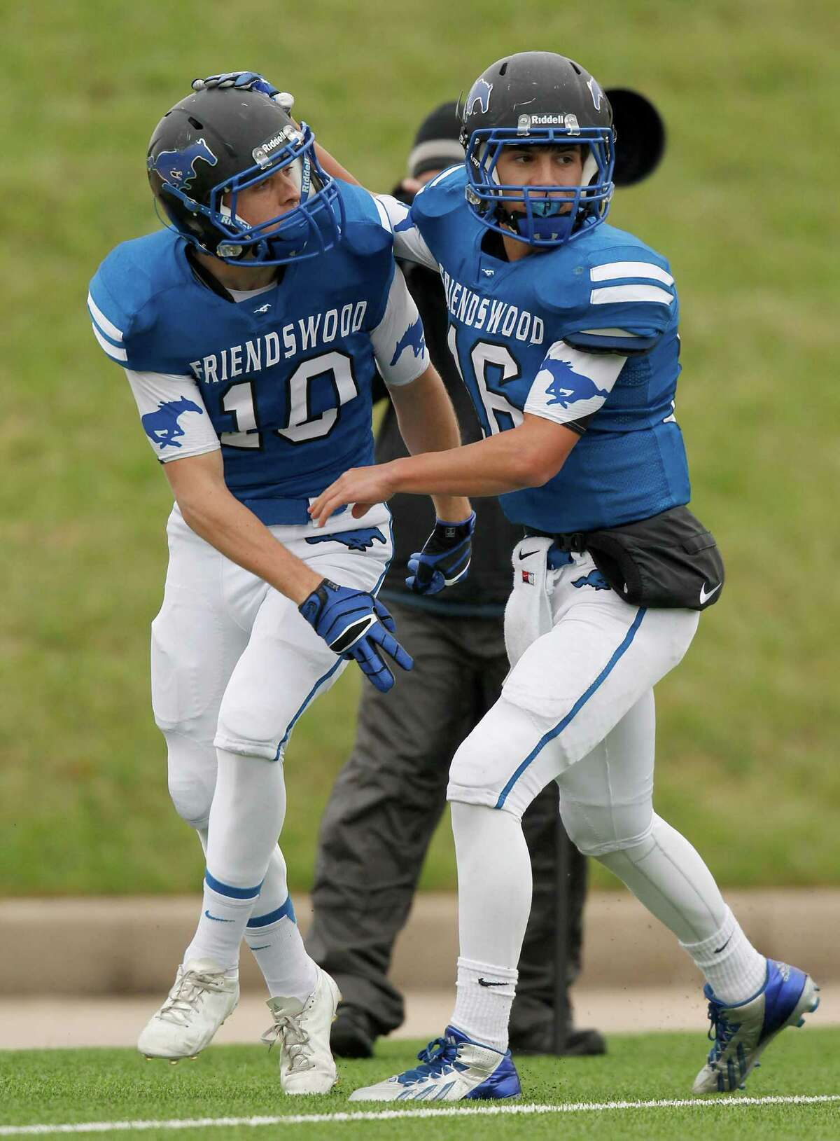 11/23/13: Friendswood Mustan Tyler Page (16) is congratulated by Roemello McCardell (10) after Page ran for 75 yard touchdown run against the Stratford Spartans in the Class 4 A Division One Play-Off game at Mercer Stadium in Sugarland, Texas. Stratford won 34 to 7.
