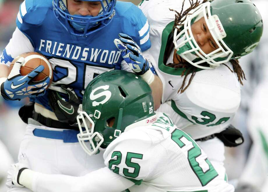 11/23/13: Friendswood Mustang Sam Longbotham (25) is tackled by Stratford Spartans Christian Osso (25) and Jajuan West (38) in the Class 4 A Division One Play-Off game at Mercer Stadium in Sugarland, Texas. Stratford won 34 to 7. Photo: Thomas B. Shea, For The Chronicle / © 2013 Thomas B. Shea