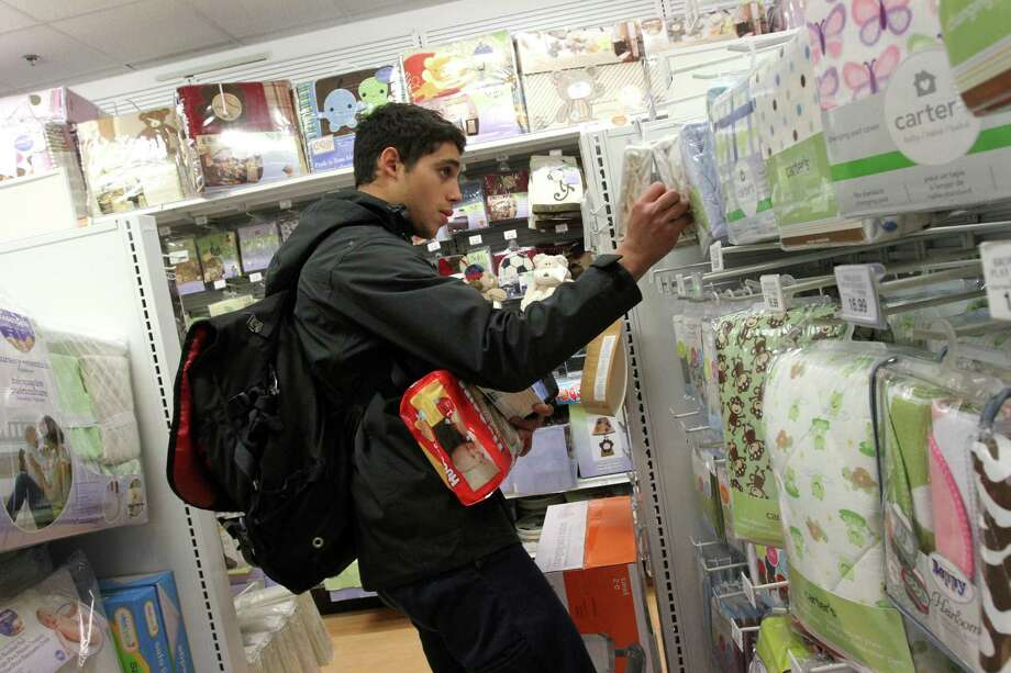 """Fermin Andujar picks up items  for a customer at Babies """"R"""" Us in New York... Nov. 8, 2013. The app for eBay Now, the company's local shopping service, promises that valets will complete a shop-and-drop-off not just in the same day but """"in about an hour,"""" a timetable crucial to the company's intensifying efforts to one-up Amazon in the delivery game. (Tina Fineberg/The New York Times) Photo: TINA FINEBERG, STR / NYTNS"""