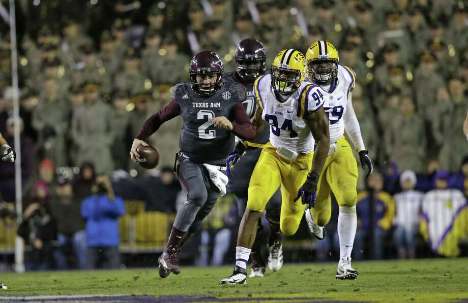 Texas A&M quarterback Johnny Manziel (2) rushes past LSU defensive end Danielle Hunter (94) in the second half of an NCAA college football game in Baton Rouge, La., Saturday, Nov. 23, 2013. LSU won 34-10. (AP Photo/Gerald Herbert) Photo: Gerald Herbert, Associated Press / AP