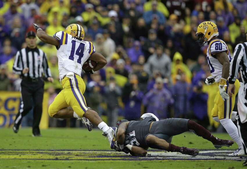 Texas A&M defensive back Howard Matthews (31) tries to tackle LSU running back Terrence Magee (14) on a long carry in the first half of an NCAA college football game in Baton Rouge, La., Saturday, Nov. 23, 2013. (AP Photo/Gerald Herbert)