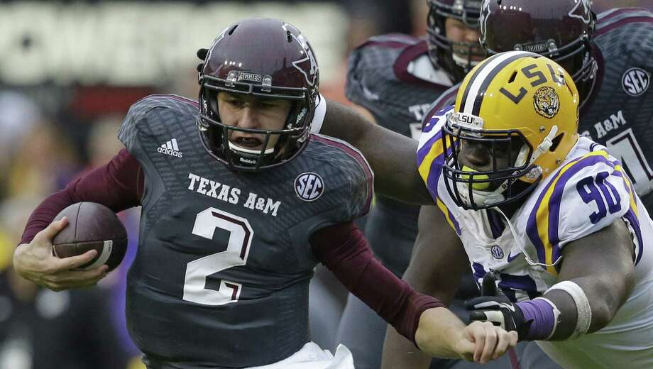Texas A&M quarterback Johnny Manziel (2) tries to elude LSU defensive tackle Anthony Johnson (90) in the first half of an NCAA college football game in Baton Rouge, La., Saturday, Nov. 23, 2013. (AP Photo/Gerald Herbert) Photo: Gerald Herbert, Associated Press / AP