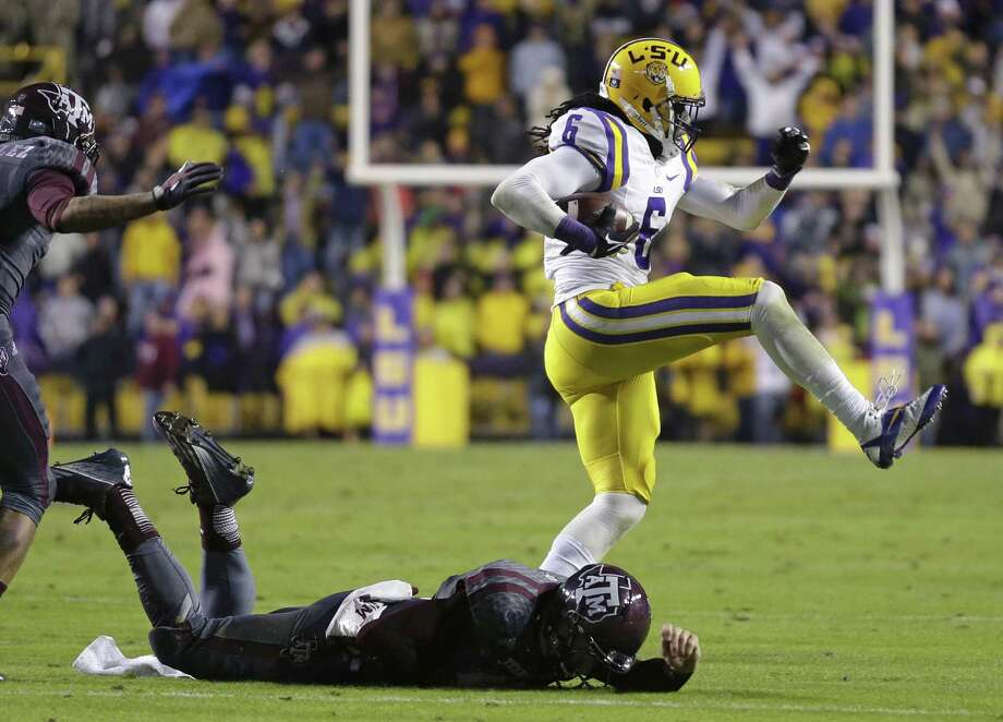 LSU safety Craig Loston (6) high-steps past Texas A&M quarterback Johnny Manziel (2) after he intercepted him in the second half of an NCAA college football game in Baton Rouge, La., Saturday, Nov. 23, 2013. LSU won 34-10. (AP Photo/Gerald Herbert) Photo: Gerald Herbert, Associated Press / AP
