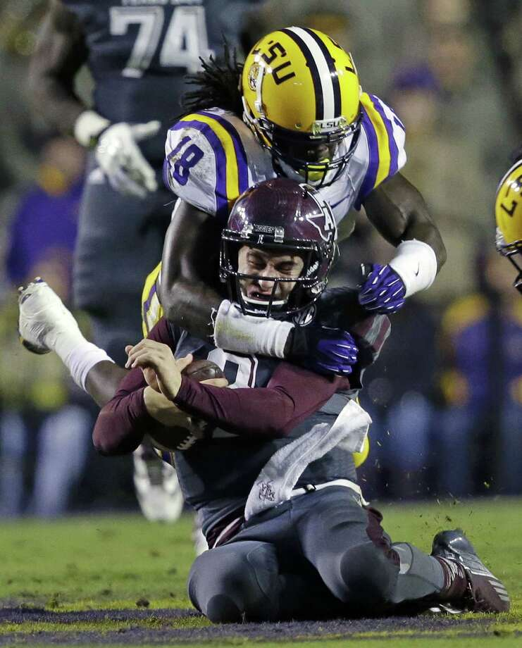 Texas A&M quarterback Johnny Manziel is tackled by LSU linebacker Lamin Barrow (18) in the second half of an NCAA college football game in Baton Rouge, La., Saturday, Nov. 23, 2013. LSU won 34-10. (AP Photo/Gerald Herbert) Photo: Gerald Herbert, Associated Press / AP