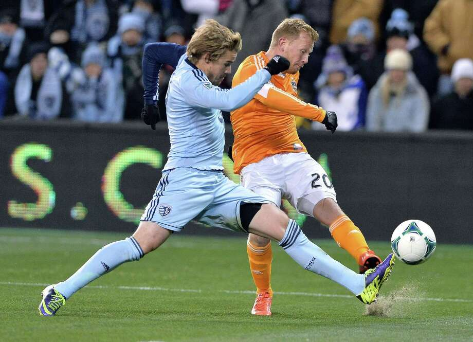 Houston Dynamo midfielder Andrew Driver (20) sends the ball past Sporting KC defender Chance Myers (7) during the first half in Kansas City, Kan., on Saturday, Nov. 23, 2013. (John Sleezer/Kansas City Star/MCT) Photo: JOHN SLEEZER, McClatchy-Tribune News Service / Kansas City Star