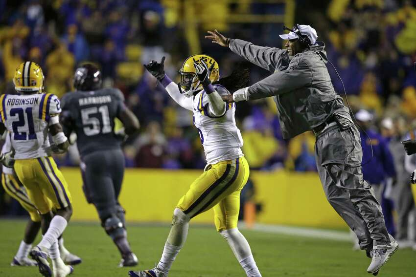 LSU safety Craig Loston (6) celebrates his interception with secondary coach Corey Raymond in the second half of an NCAA college football game against Texas A&M in Baton Rouge, La., Saturday, Nov. 23, 2013. LSU won 34-10. (AP Photo/Gerald Herbert)