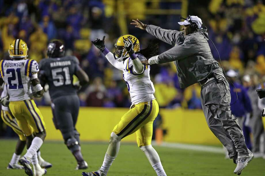 LSU safety Craig Loston (6) celebrates his interception with secondary coach Corey Raymond in the second half of an NCAA college football game against Texas A&M in Baton Rouge, La., Saturday, Nov. 23, 2013. LSU won 34-10. (AP Photo/Gerald Herbert) Photo: Gerald Herbert, Associated Press / AP