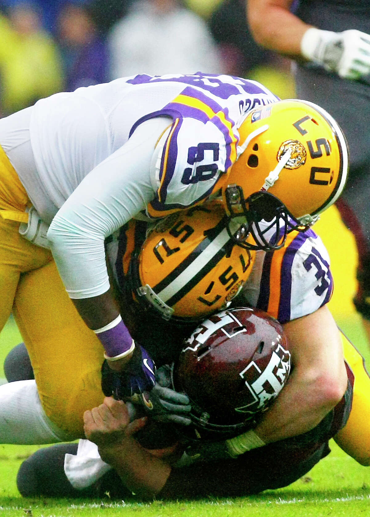 LSU defensive end Jermauria Rasco, top, and linebacker D.J. Welter wrap up Texas A&M quarterback Johnny Manziel during the second quarter of an NCAA College football game at Tiger Stadium Saturday, Nov. 23, 2013, in Baton Rouge. LSU won 34-10.
