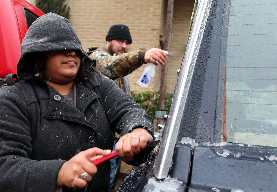 Samantha Hernandez scrapes ice off of the windows after Kenneth Fields sprays them with a concoction of vinegar and water to soften the ice on Saturday, Nov. 23, 2013, in Odessa, Texas. The fierce weather has caused at least eight deaths and prompted advisories Saturday afternoon in New Mexico and Texas. Photo: Edyta Blaszczyk, Odessa American / Odessa American