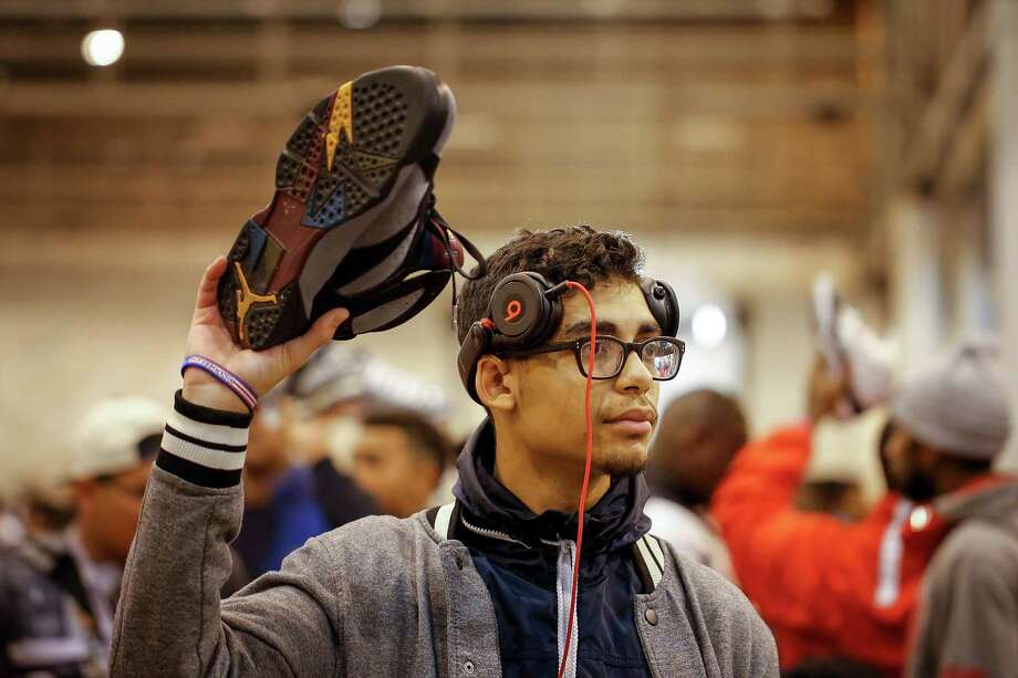 Matthew Guillory of Houston holds up a pair of sneakers in an attempt to find a buyer during the 2013 fall Sneaker Summit, Saturday, November 23, 2013 at Reliant Center in Houston. The event is the world's largest and original community-based sneaker event. Sneaker enthusiasts from all across the globe flock to the Houston event to buy, sell, and trade sneakers and fashions and accessories. Photo: © TODD SPOTH, 2013 / © TODD SPOTH, 2013