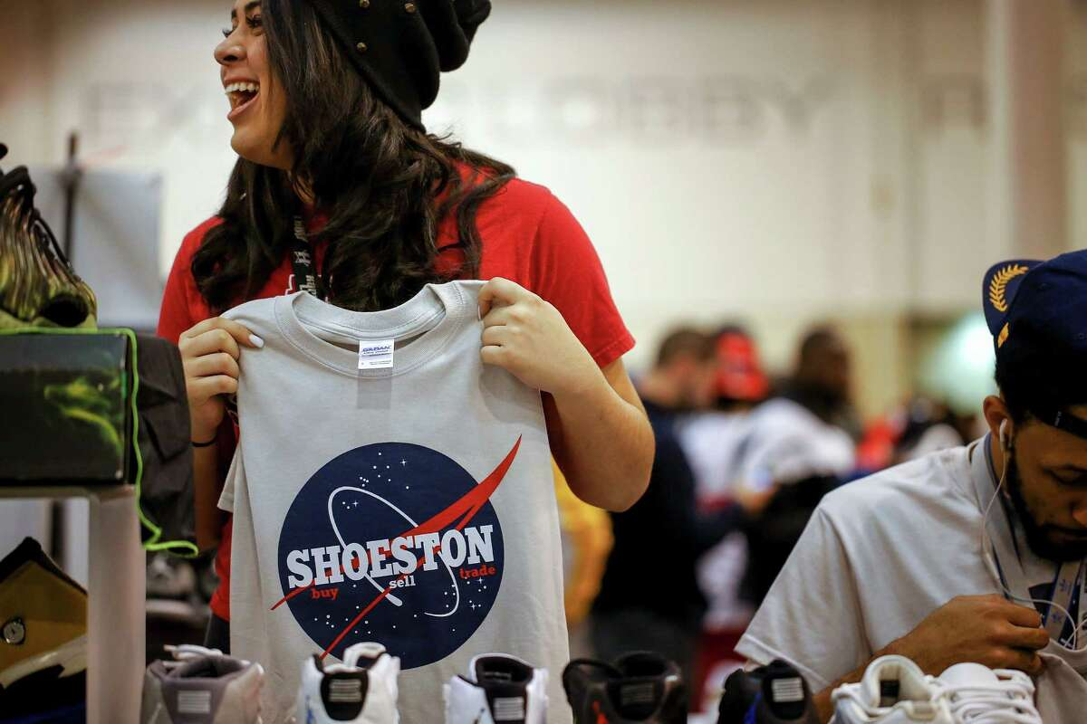Amanda Lopez of Shoeston, a local business that buys, sells and trades shoes holds up a Shoeston shirt, during the 2013 fall Sneaker Summit.