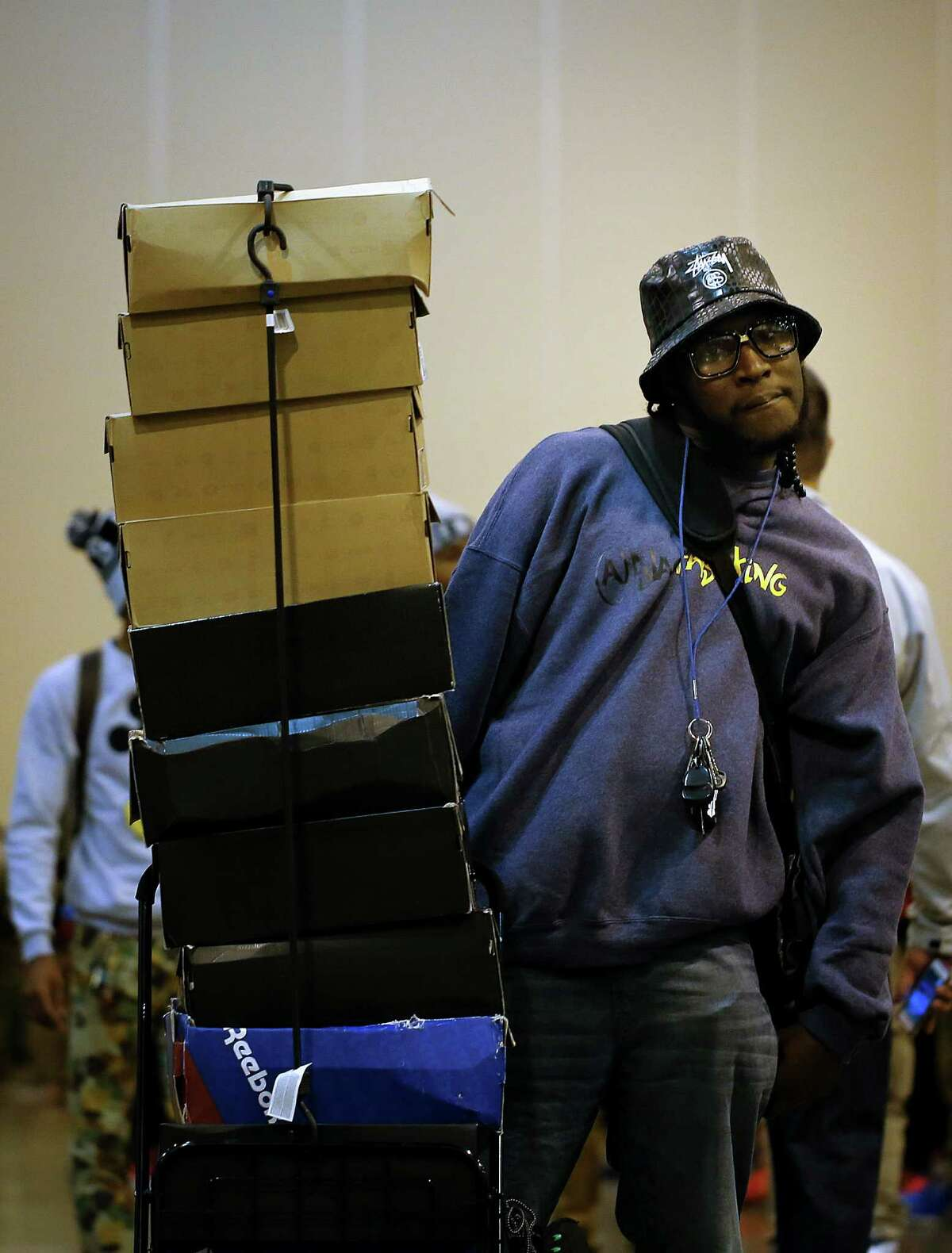 Jay Rotiri poses for a photo next to his cart of shoes for sale, stacked tall, during the 2013 fall Sneaker Summit.