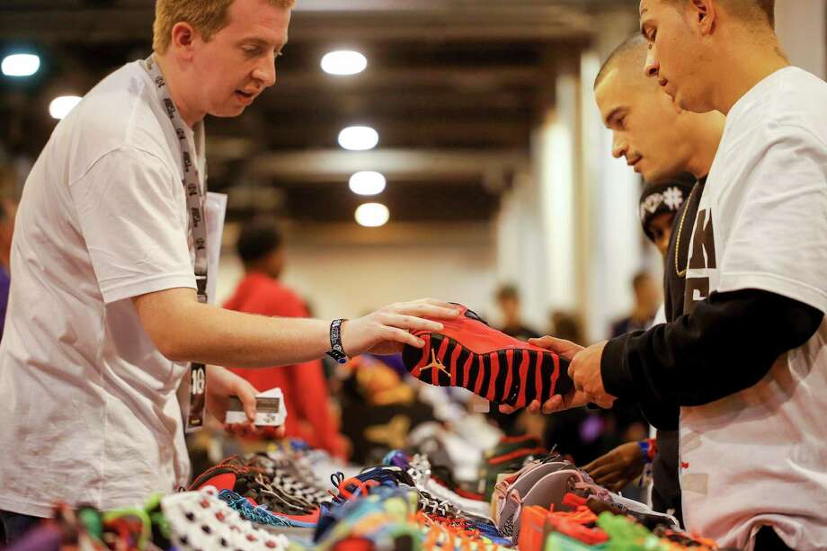 Drew Kelso of Step by Step Sneakers helps Houston residents, Daniel Dalardo, right, and friend, Javier Lopez, check out shoes, during the 2013 fall Sneaker Summit. Photo: © TODD SPOTH, 2013 / © TODD SPOTH, 2013