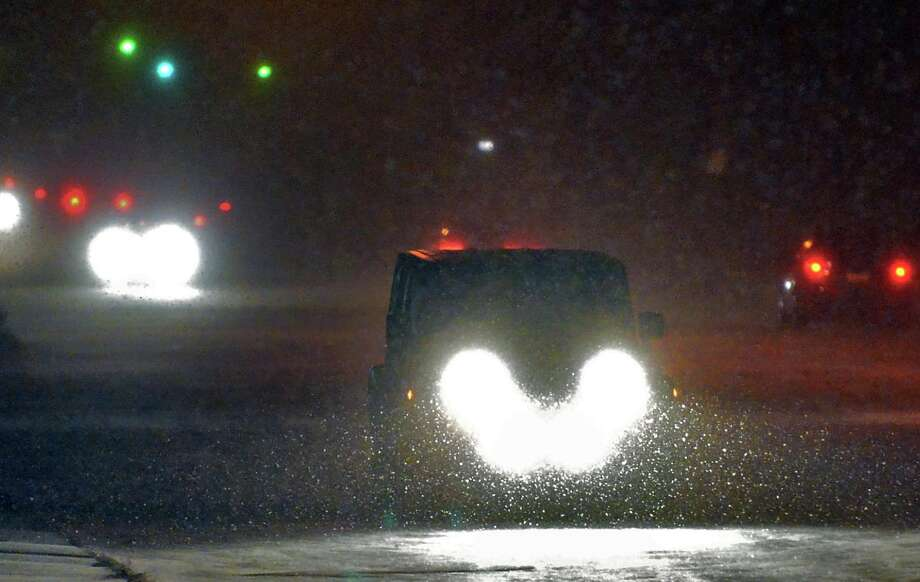 Cars wend their way through the first snow flurries of the season along Western Avenue Saturday night Nov. 23, 2013, in Albany, NY.  (John Carl D'Annibale / Times Union) Photo: John Carl D'Annibale