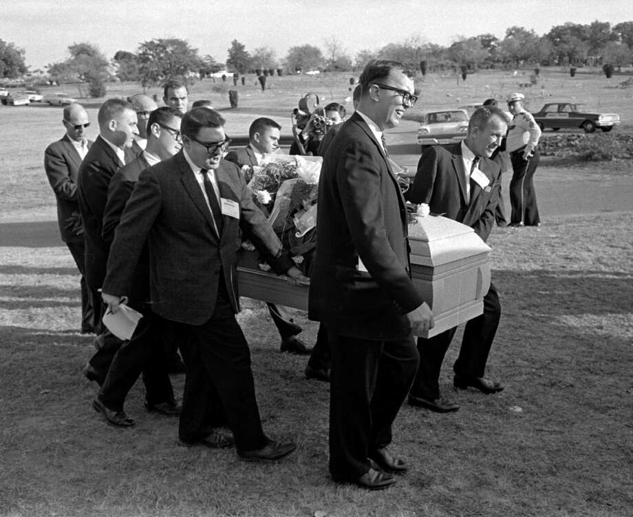 Reporters were enlisted to act as pallbearers at the interment of Lee Harvey Oswald at the Rose Hill Cemetery. Pallbearers, from left end - Jerry Flemmons with crew cut and no glasses. In front of Flemmons are reporters Ed Horn and Mike Cochran. Funeral director Paul J. Groody was among the pallbearers. On the far side of the casket are Jon McConal, rear, and Preston McGraw, front. Photo: Gene Gordon, HONS / Gene Gordon