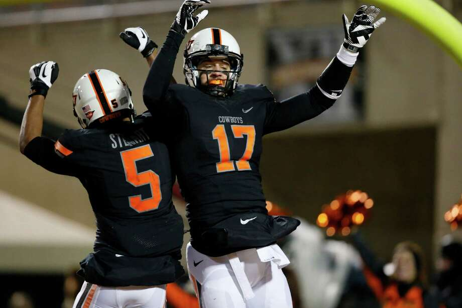 Oklahoma State wide receiver Charlie Moore (17) celebrates a touchdown against Baylor with teammate Josh Stewart (5) in the second quarter of an NCAA college football game in Stillwater, Okla., Saturday, Nov. 23, 2013. (AP Photo/Sue Ogrocki) Photo: Sue Ogrocki, Associated Press / AP