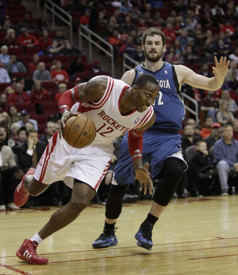 Rockets power forward Dwight Howard (12) drives around Timberwolves power forward Kevin Love (42). Photo: Bob Levey, Houston Chronicle
