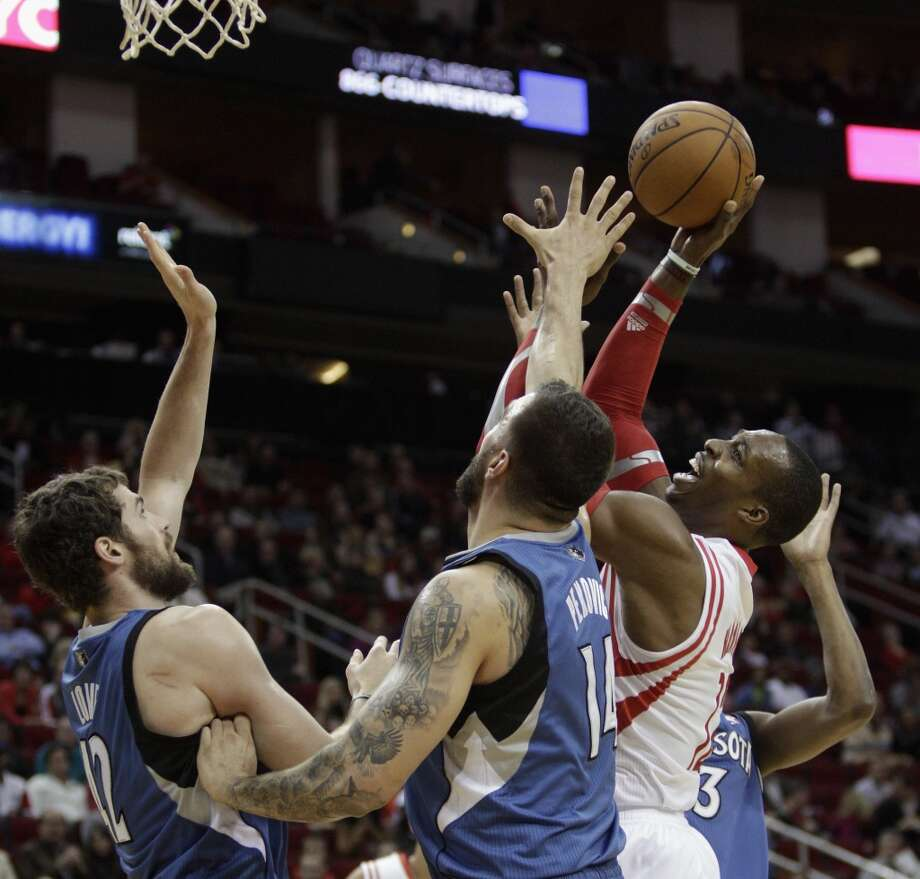 Rockets power forward Dwight Howard (12) shoots over Timberwolves center Nikola Pekovic (14) and power forward Kevin Love (42). Photo: Bob Levey, Houston Chronicle