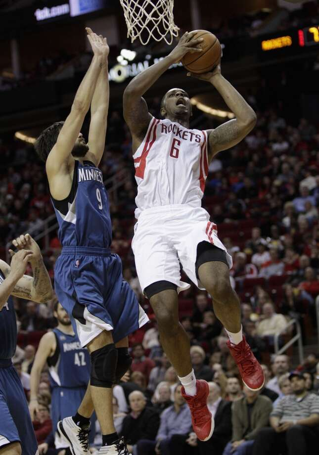 Rockets power forward Terrence Jones (6) drives to the basket over Timberwolves point guard Ricky Rubio (9). Photo: Bob Levey, Houston Chronicle