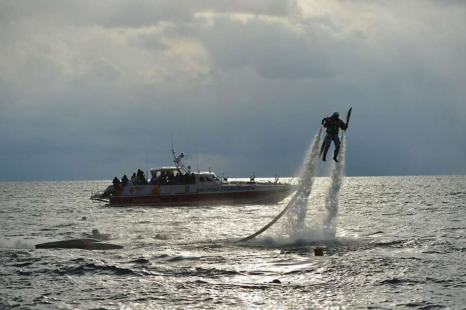 In this photo provided by  Olympictorch2014.com Olympic torch bearer Mikahil Chuyev using a jet pack carries an Olympic torch from a boat to the shore during the Olympic torch relay on Lake Baikal in Siberia, Russia, Saturday, Nov. 23, 2013. The Olympic torch has plunged into Russia's Lake Baikal in the run-up to the Sochi Winter Games. The 65,000-kilometer (39,000 mile) Sochi torch relay, which started on Oct. 7, is the longest in Olympic history. The torch has traveled to the North Pole on a Russian nuclear-powered icebreaker and has even been flown into space.  (AP Photo/Olympictorch2014.com) Photo: Olympictorch2014.com, Associated Press