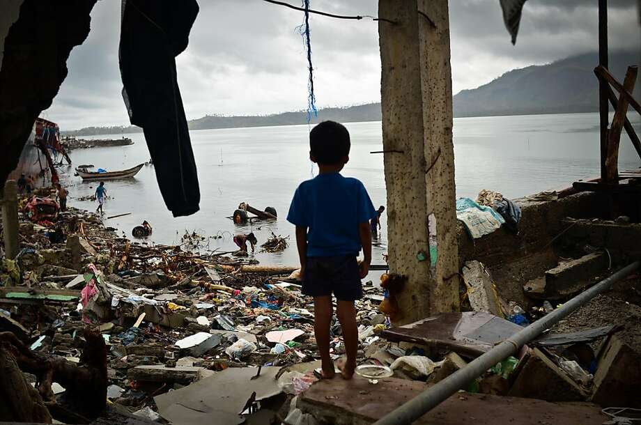 TACLOBAN, LEYTE, PHILIPPINES - NOVEMBER 23:   A boy peers out of a damaged structure near the shoreline on November 23, 2013 in Tacloban, Leyte, Philippines. Bodies continue to be recovered nearly two weeks after the devastating Typhoon Haiyan hit as the official death toll now exceeds 5,000. The typhoon has been described as one of the most powerful to ever to hit land, leaving thousands dead and hundreds of thousands homeless. Countries all over the world have pledged relief aid to help support those affected by the typhoon, but damage to the airport and roads have made moving the aid into the most affected areas very difficult.  (Photo by Dondi Tawatao/Getty Images) *** BESTPIX *** Photo: Dondi Tawatao, Getty Images