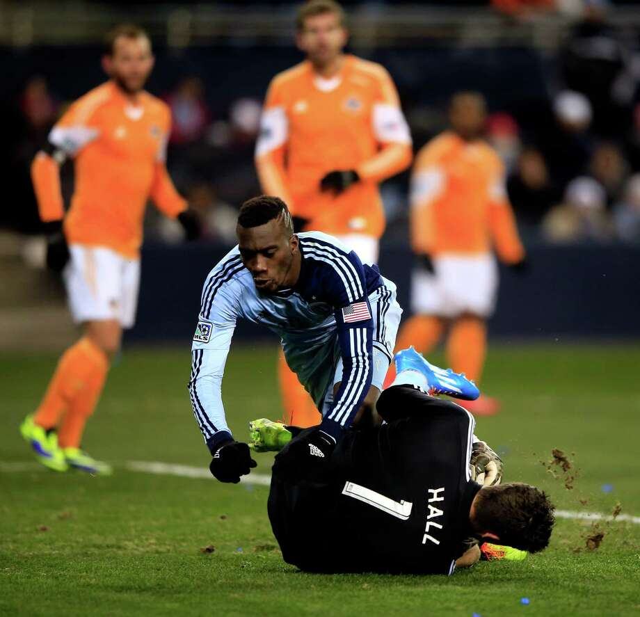 Sporting Kansas City's C.J. Sapong, who tied the match in the 14th minute, tumbles over Dynamo goalkeeper Tally Hall as he makes a save Saturday night. Photo: Jamie Squire, Staff / 2013 Getty Images