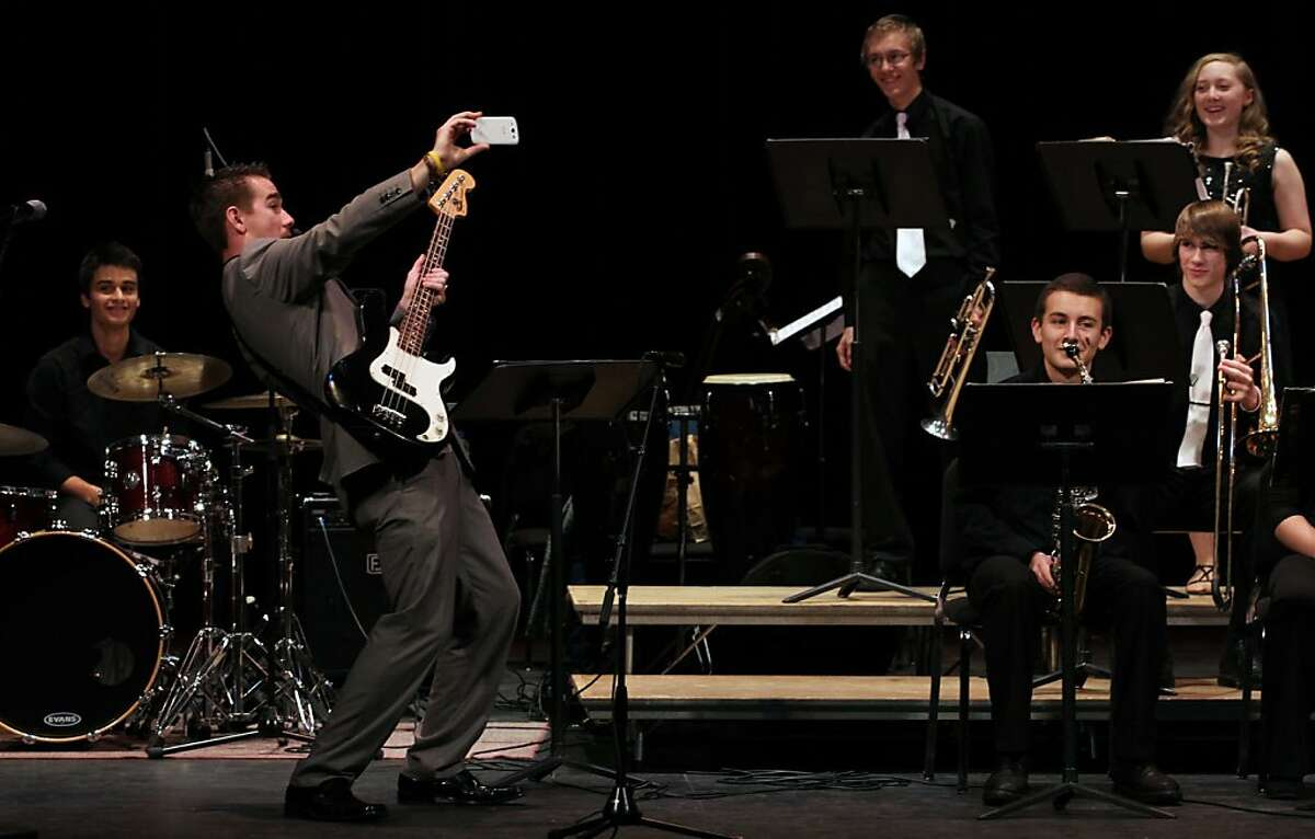 Tenino High School jazz band director Andrew Bowerly draws a few laughs as he contorts to catch a group photo on stage before the start of their performance on Saturday, Nov. 23, 2013, in Olympia,Wash. The performance was part of a fundraiser to help build international clean water projects, buy and refurbish instruments for four local school district music programs and promote a youth leadership training course. (AP Photo/The Olympian, Steve Bloom)