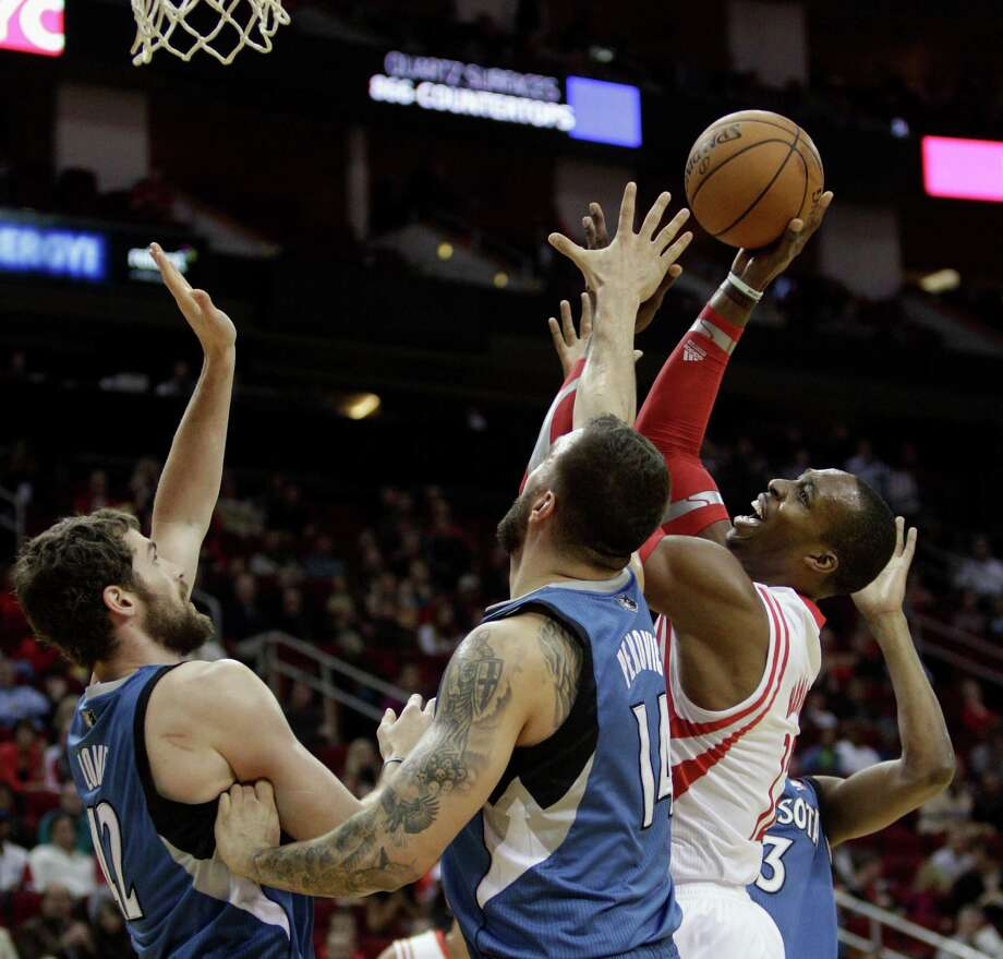 Rockets power forward Dwight Howard, right, had his hands full with Timberwolves big men Nikola Pekovic, center, and Kevin Love on Saturday night, but he was able to hold his own to the tune of 11 points and 13 rebounds in the Rockets' 112-101 win at Toyota Center. Photo: Bob Levey, Special To The Chronicle / ©2013 Bob Levey