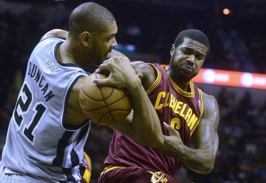 Tim Duncan of the San Antonio Spurs fights for the ball against Earl Clark, right, of the Cleveland Cavaliers during NBA action in the AT&T Center on Saturday, Nov. 23, 2013. Duncan was able to immediately shoot and sink a shot. Photo: Billy Calzada, San Antonio Express-News