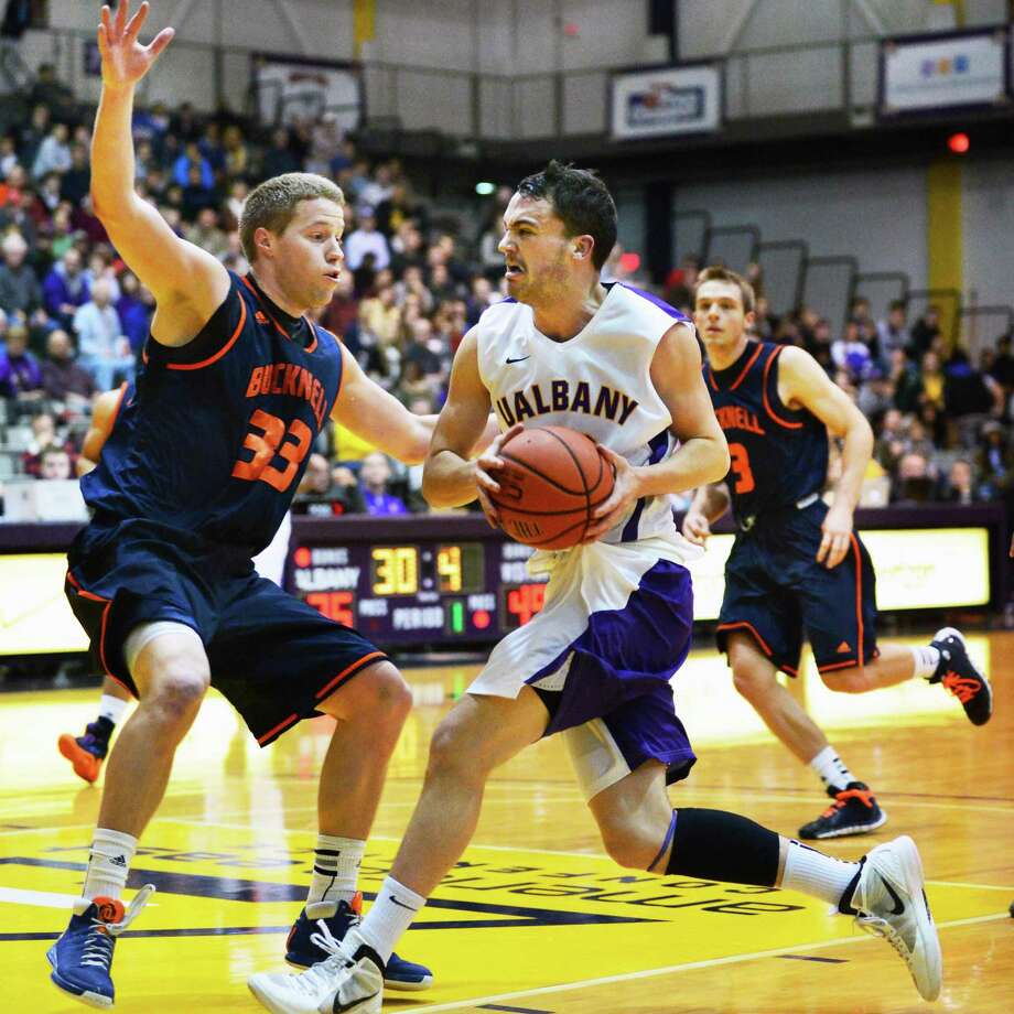 UAlbany's #12 Peter Hooley drives past Bucknell's #33 Ben Brackney during Saturday's game at the Sefcu Arena Nov. 23, 2013, in Abany, NY.  (John Carl D'Annibale / Times Union) Photo: John Carl D'Annibale / 00024711A