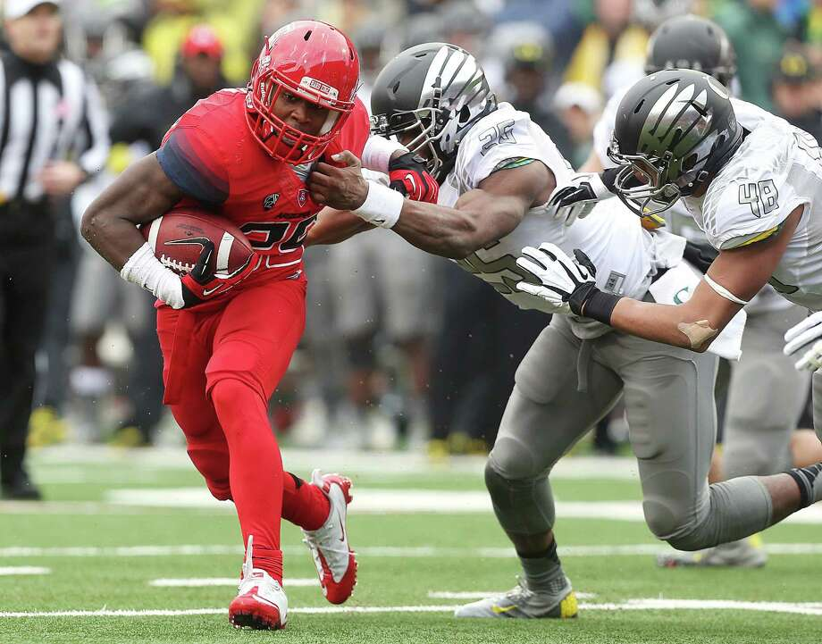 Arizona running back Ka'Deem Carey (25) tries to slip around Oregon linebacker Boseko Lokombo (25) during the first quarter of an NCAA college football game on Saturday, Nov. 23, 2013, at Arizona Stadium in Tucson, Ariz. (AP Photo/Arizona Daily Star,  Mike Christy)  ALL LOCAL TV OUT; PAC-12 OUT; MANDATORY CREDIT ORG XMIT: AZTUS105 Photo: Mike Christy / Arizona Daily Star