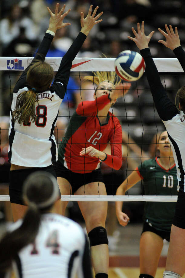 Rachel Reed (center) of Conroe The Woodlands slams a spike between Churchill's Taylor Martinez (left) and a teammate during their Class 5A championship match at the Culwell Center in Garland on Saturday. The Highlanders defeated the Chargers 25-22, 26-24, 25-17 to complete a 45-0 season. Churchill wound up 47-3. Photo: For The Express-News