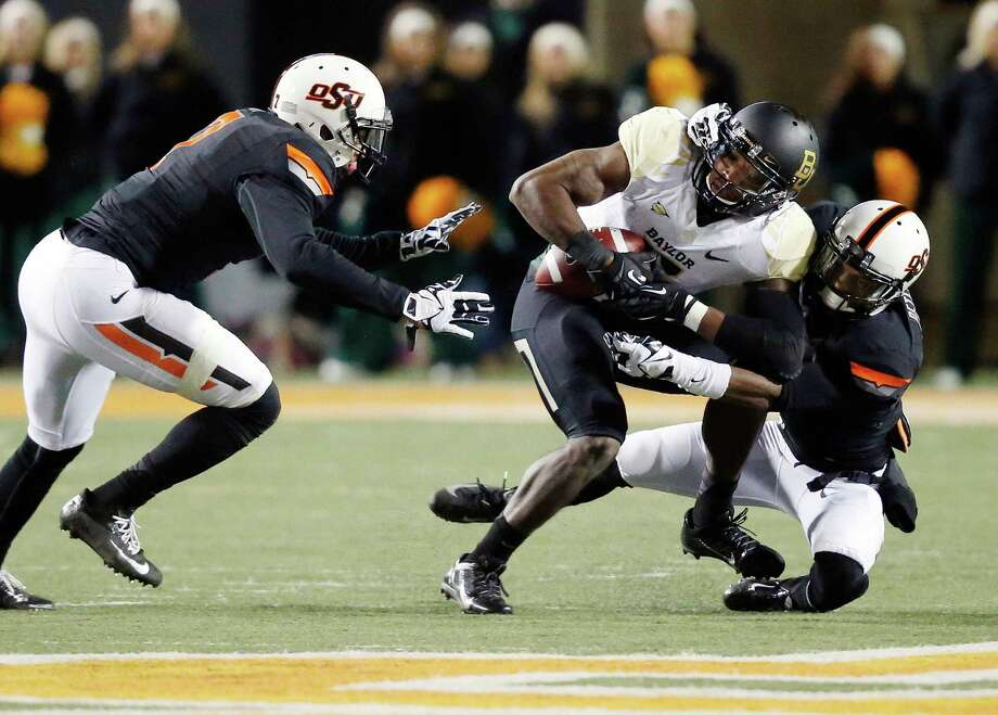 Baylor wide receiver Antwan Goodley (5) is tackled by Oklahoma State cornerback Kevin Peterson, right, in the second quarter of an NCAA college football game in Stillwater, Okla., Saturday, Nov. 23, 2013. (AP Photo/Sue Ogrocki) Photo: Sue Ogrocki, Associated Press / AP