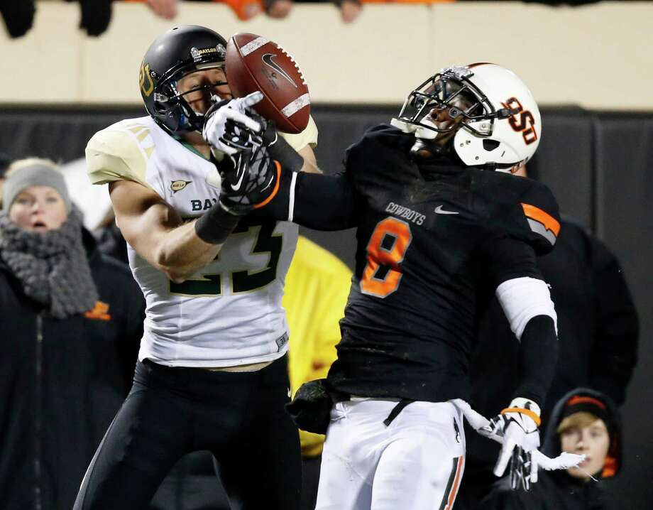 Oklahoma State safety Daytawion Lowe (8) breaks up a pass intended for Baylor wide receiver Clay Fuller (23) in the second quarter of an NCAA college football game in Stillwater, Okla., Saturday, Nov. 23, 2013. (AP Photo/Sue Ogrocki) Photo: Sue Ogrocki, Associated Press / AP