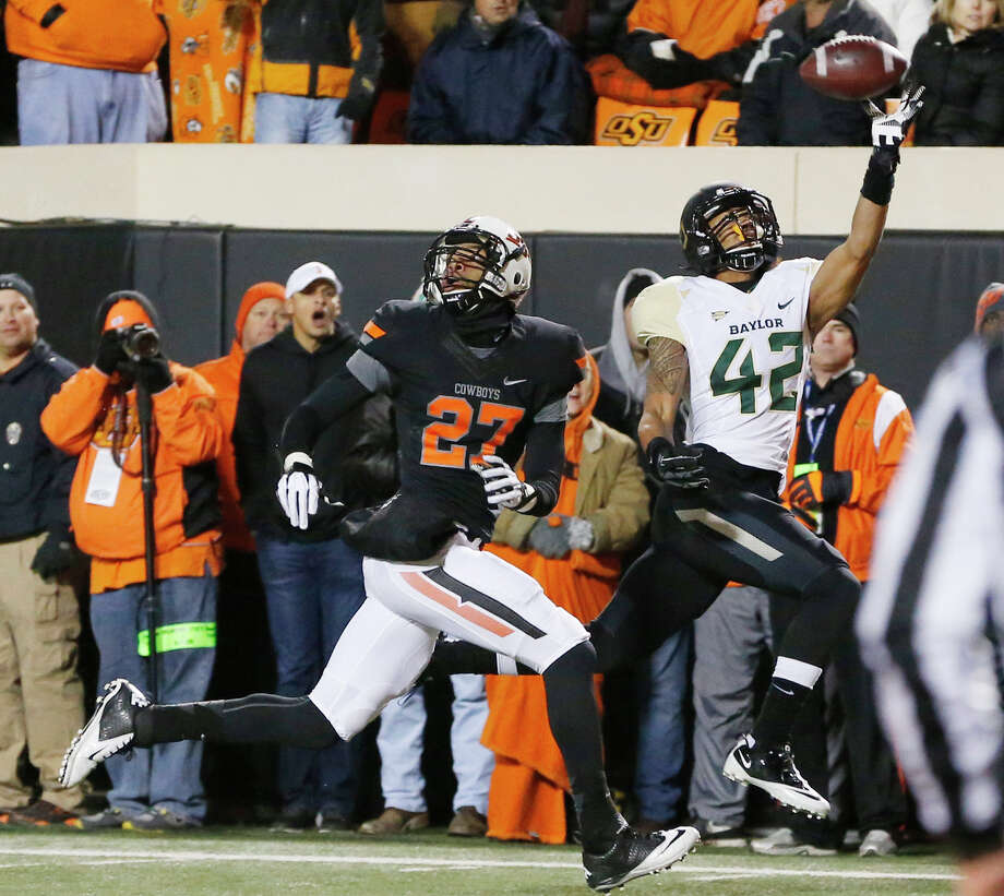 Baylor receiver Levi Norwood (42) can't make the catch on a pass in front of Oklahoma State safety Lyndell Johnson (27) in the second quarter of an NCAA college football game in Stillwater, Okla., Saturday, Nov. 23, 2013. (AP Photo/Sue Ogrocki) Photo: Sue Ogrocki, Associated Press / AP