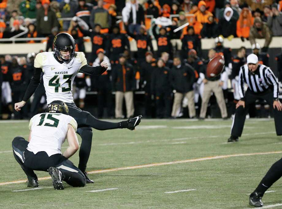 Baylor kicker Aaron Jones (43) kicks a field goal against Oklahoma State in the second quarter of an NCAA college football game in Stillwater, Okla., Saturday, Nov. 23, 2013. Baylor's Brody Trahan (15) holds. (AP Photo/Sue Ogrocki) Photo: Sue Ogrocki, Associated Press / AP