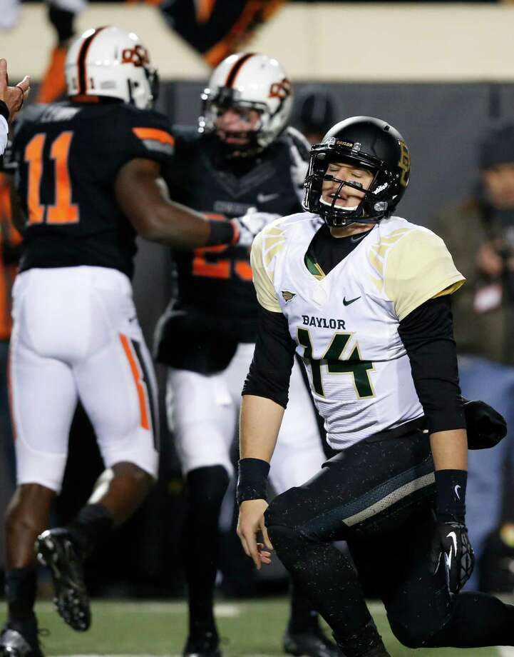 Baylor quarterback Bryce Petty (14) gets up as Oklahoma State defenders Shaun Lewis (11) and Zack Craig (23) celebrate a sack of Petty in the second quarter of an NCAA college football game in Stillwater, Okla., Saturday, Nov. 23, 2013. (AP Photo/Sue Ogrocki) Photo: Sue Ogrocki, Associated Press / AP
