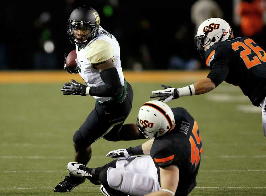 Baylor wide receiver Antwan Goodley (5) carries the ball past Oklahoma State defenders Caleb Lavey (45) and Tyler Patmon (26) in the first quarter of an NCAA college football game in Stillwater, Okla., Saturday, Nov. 23, 2013. (AP Photo/Sue Ogrocki) Photo: Sue Ogrocki, Associated Press / AP