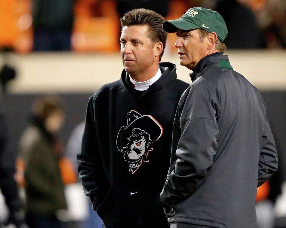 Baylor head coach Art Briles, left, and Oklahoma State head coach Mike Gundy, right, talk before the start of their NCAA college football game in Stillwater, Okla., Saturday, Nov. 23, 2013. (AP Photo/Sue Ogrocki) Photo: Sue Ogrocki, Associated Press / AP